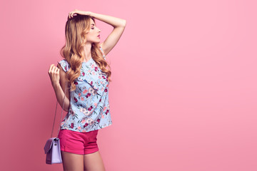 Gorgeous confident woman in spring summer Trendy outfit, fashionable glamour makeup, accessories. Portrait sexy beautiful blonde model girl posing in Studio on pink.