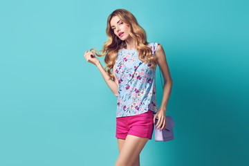 Fashion beautiful young happy woman in floral blouse, shorts with handbag over blue background. Adorable girl with Stylish wavy Hairstyle, fashionable makeup.