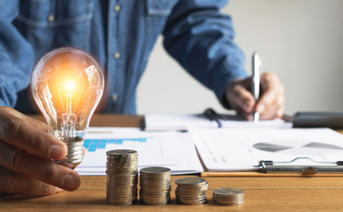 Business man holding light bulb and some coins on table writing  saving bank and account for his money all in finance accounting concept.
