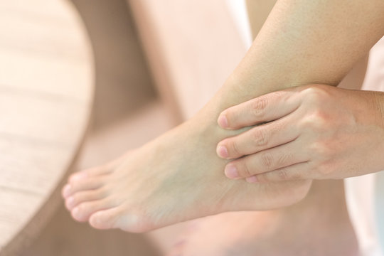 Achilles tendon injury concept. Hands on foot ankle with red spot as pain and swelling up from rupture or tear.