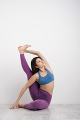 Young brunette woman in purple leggings and a sports t-shirt does exercises on the floor. Balances on the blocks and near the wall. White room.