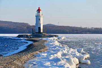 Russia. Vladivostok. The  lighthouse of Egersheld(1876 year built) Tokarevskaya koshka in winter evening in Amur bay