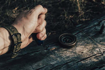 Man dirty hand holds a knife, a compass on an old log in forest.Survival.