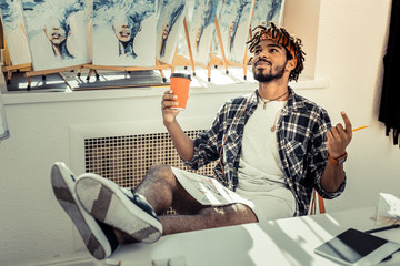 Young artist with dreadlocks feeling emotional having new ideas