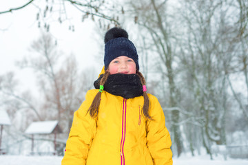 winter portrait of little girl with pigtails in  jacket and blue hat in winter