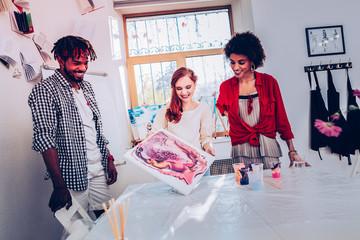 Three cheerful workers of art department feeling satisfied