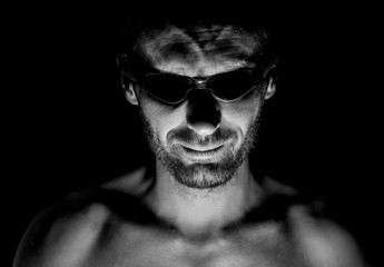 Portrait of unshaven adult caucasian man in swimming glasses. He smiles and looks straight to watcher. Black and white shot, low-key lighting. Isolated on black.