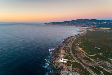 Aerial view of the Guincho area, with the Cabo Raso Lighthouse, the scenic road along the coast and the Roca Cape (Cabo da Roca) on the background;