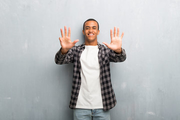 Young african american man with checkered shirt counting nine with fingers