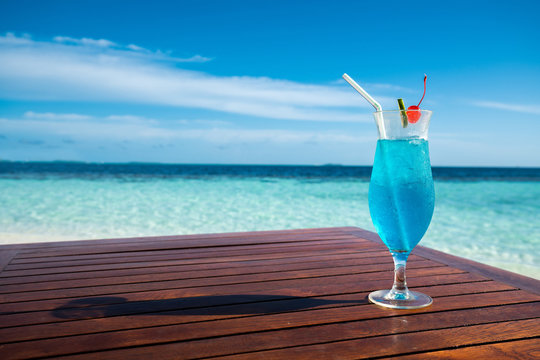 Blue lagoon cocktail on table and beautiful sea background