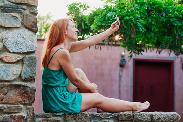 Young tourist woman taking a selfie in a Greek village