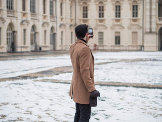 Handsome trendy man wearing elagant jacket using cell phone to take photos, outdoor in city setting in winter day shot