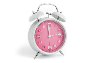 Table alarm clock with time 1 minute to 12 hours with pink clock face, 11.59 AM PM, on white background
