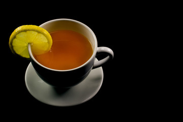 Tea with lemon in a white cup on a black background
