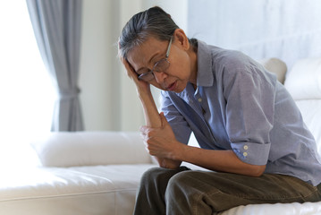 Mature Asian senior woman sitting on a white sofa at home touching her head with her hands while having a headache pain and feeling unwell due to sickness and stress. Senior health concern concept.