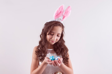 Happy girl  with easter eggs on white background. Bunny's ears