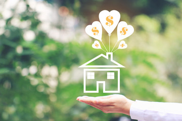 Female hands holding symbol of house with balloon and symbol of dollar on natural green background, Save money for prepare in future and Banking concept
