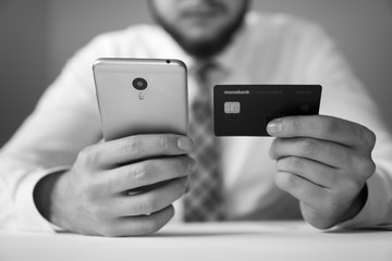Online trading on the currency exchange. Young businessman with a bank credit card in his hands. Payment of goods online. Online payments through the phone. Smartphone and Internet Commerce.