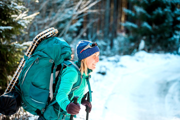 Woman with backpack and snowshoes in the winter mountains.