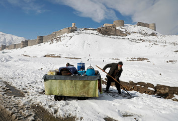 An Afghan man removes snow next to his handcart after the first snow in winter on the snow-covered ground in Kabul, Afghanistan