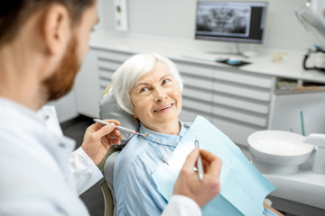 Elderly woman during the medical examination with male dentist in the dental office