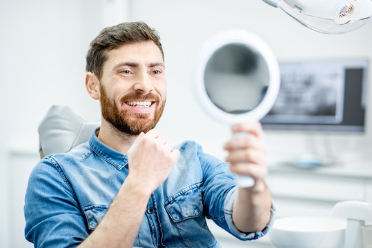 Portrait of a handsome bearded man with healthy smile in the dental office