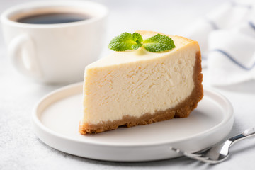 Tasty Plain New York Cheesecake Decorated With Mint Leaf. Cup of Coffee On Background