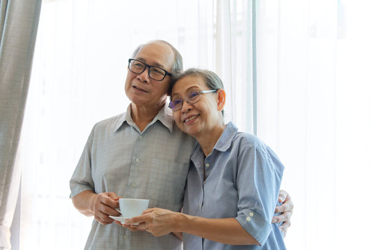 Asian senior couples standing together while they looking in front of them with smile showing they have happy life after retirement together. Wife is serving coffee to her husband.