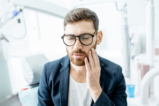 Businessman having a toothache waiting for the doctor in the dental office