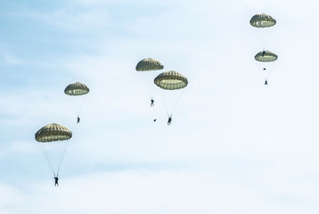 Many soldiers with parachutes in the sky.