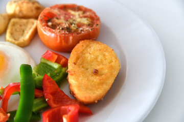 Breakfast with scrambled eggs, fried buns and vegetables