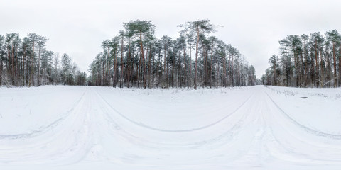 Winter full spherical 360 degrees angle view panorama road in a snowy forest with gray pale sky in equirectangular projection. VR AR content