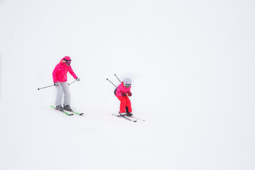 Mother and daughter skiing in a winter snowy day on a mountain