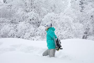 Girl with a snowboard walking through deep snow in a mountain