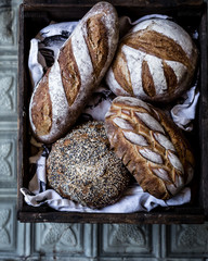 basket of bread loaves on metal tiled surface