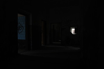 Dark corridor of abandoned decay building with light shining from rooms, urbex