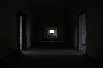 Dark corridor of abandoned decay building with few light, urbex