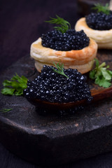 Black caviar in a wooden spoon and puff pastry tartlets on a dark board