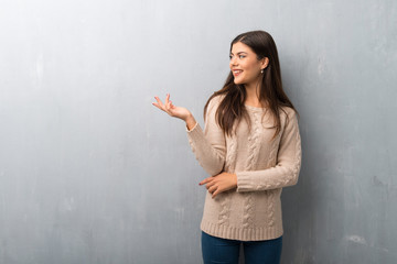 Teenager girl with sweater on a vintage wall extending hands to the side for inviting to come