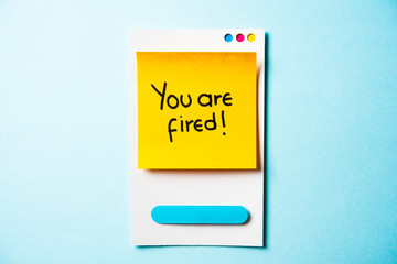YOU'RE FIRED text with paper smart phone concept on blue background. Paper card with illustration.