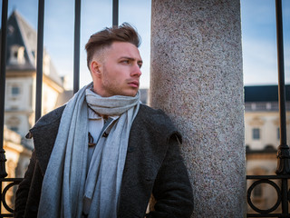 One handsome young man in urban setting in European city, standing, wearing black coat and scarf in winter day