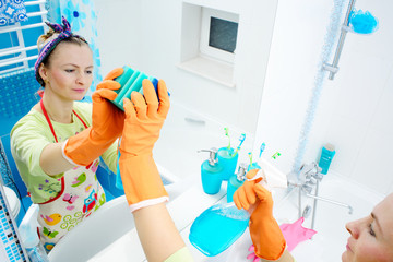 A woman polishing mirror using a cleaning sponge and rubber gloves cleaning a mirror with a spray cleaner