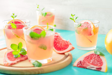 Pink alcoholic cocktail with grapefruit, ice and min