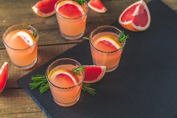 Pink cocktail with grapefruit, ice and rosemary