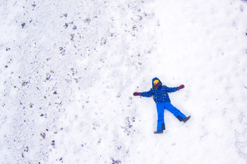 Young boy lying on the snow. Aerial view.