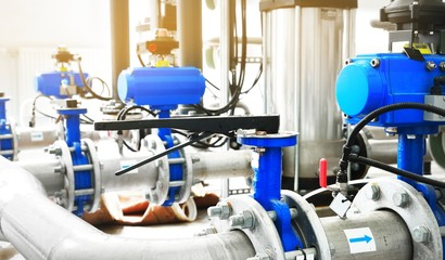Large industrial water treatment and boiler room. Shiny steel metal pipes and blue pumps and valves.