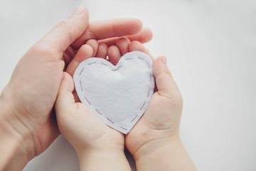 adult and child hands holding white heart, health care, donate and family insurance concept, world heart day, world health day, family love concept.