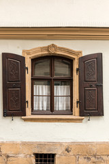 Old window made of stone and wood with brown shutters