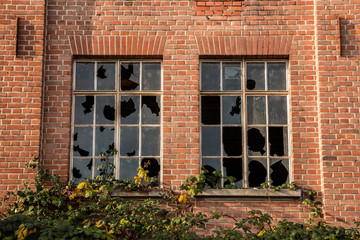 Old destroyed brick house ruin with broken windows