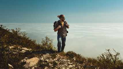 Hiking Man climbing to the top and looks to the side of the clouds. Motivation, travel, search, scout, wanderlust, tourism concept